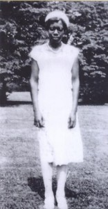 A young african american woman with glasses in a white knee-length dress in a garden