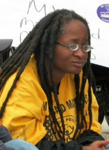 Image: Anita Cameron. An African American womyn with glasses, a yellow shirt and long dreads.
